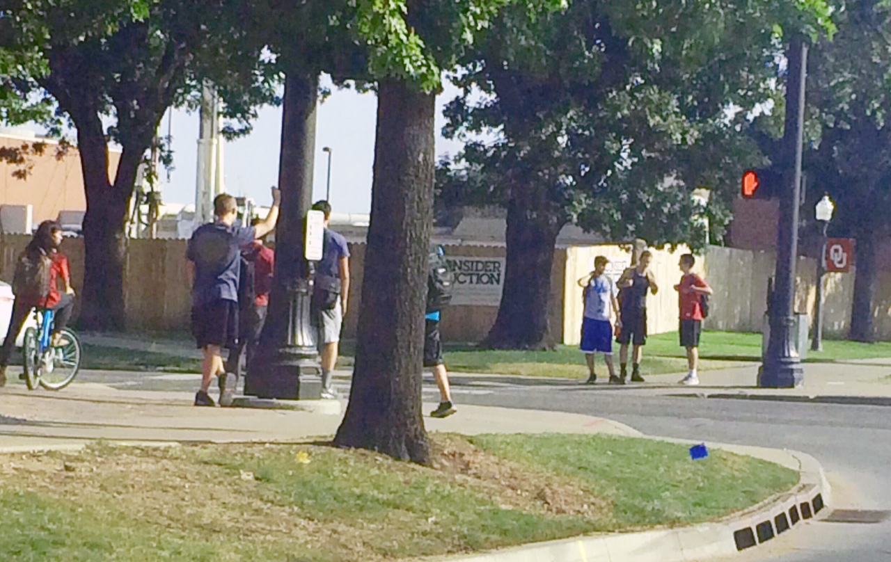 Students wait at a busy crosswalk at Lindsey and Asp on the OU campus.